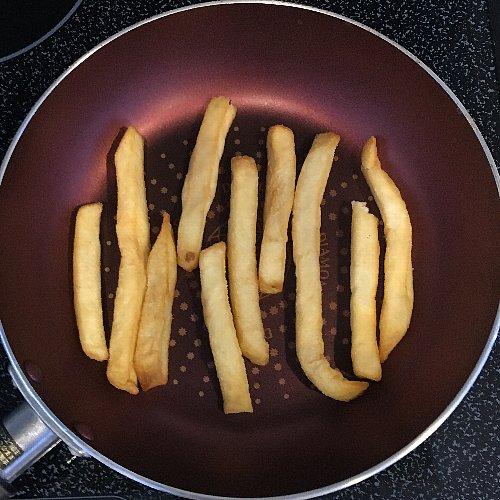 フライパンで温め直されているポテト